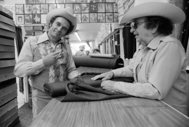ca. 1970's, Los Angeles, California, USA --- Haggard choosing fabric for a new Nudie outfit. --- Image by © Jeff Albertson/CORBIS